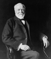 800px-Andrew Carnegie, three-quarter length portrait, seated, facing slightly left, 1913.jpg